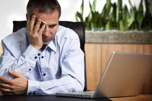 Frustrated Account Manager at laptop.